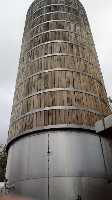 A photograph of hot water thermal storage in Islington. The tank is a tall cylindor of wood, with metal straps going around it at even intervals.