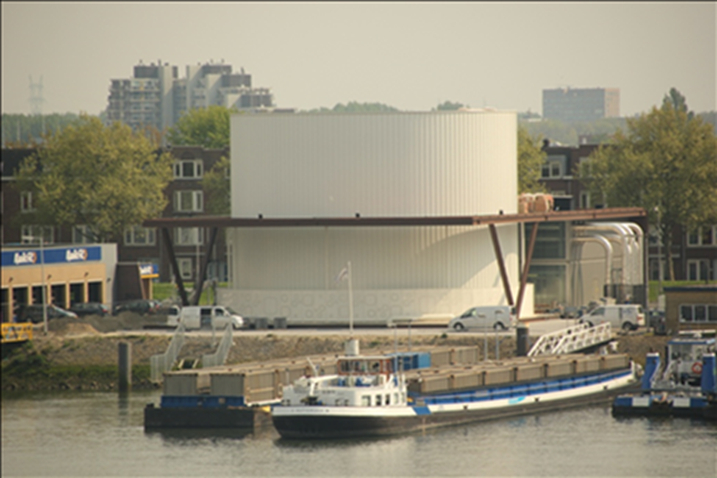 A photograph of The Heat Hub demonstrator in Rotterdam. It's by the water and you can see some boats in the lower edge of the images. In the far background there's a skyline with higher buildings.