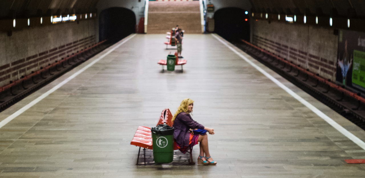 Photograph of the Titan Metro Station in Bucharest. It's taken from the side of a large tunnel, showing the long platform and some passangers waiting for trains. Train tracks run on boths sides of the platform. A woman sitting in the foreground of the photo is in focus and the background is slightly blurred.