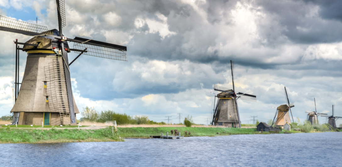 Photograph of five windmills on a grassy field next to water. The photo is taken from a perspective where the first mill looks significantly bigger than the second one, etc, until the last windmill in the distance. There sky above is filled with clouds.