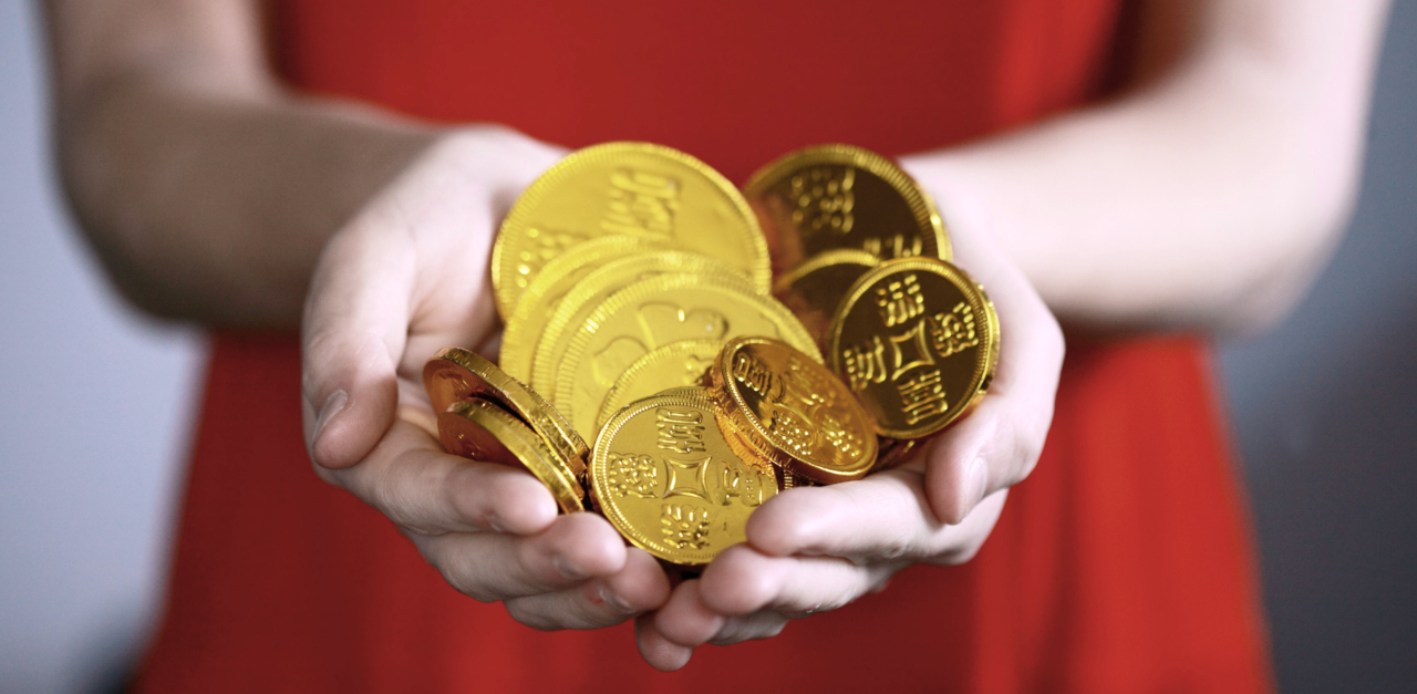 Person in a bright red dress holding out their hands in front of them and holding a small pile of golden coins.