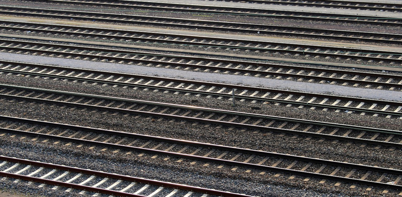 photograph of many train tracks, running side by side. Nothing else is visible except the train tracks and earth between them.