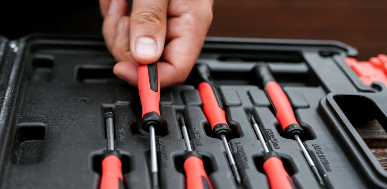 Photograph of a hand grabbing a screwdriver from out of a toolbox or toolset that is open on a table. There are several similar screwdrivers lying next to the one being held by the hand.