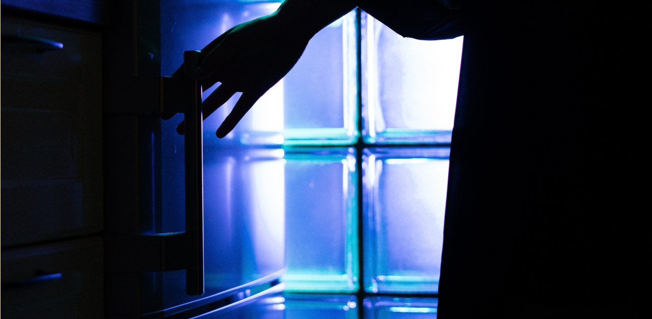 The siluette of a torso and a hand reaching for a refrigerator handle, in black against a backdrop of blue light shining through a glass wall.